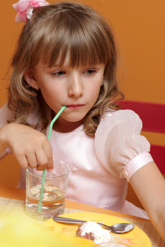 The girl drinks water in the cafe