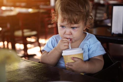 Cute sad child drinking water in restaurant.