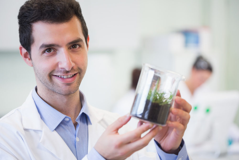 Portrait of a smiling young male researcher holding young plant at the laboratory