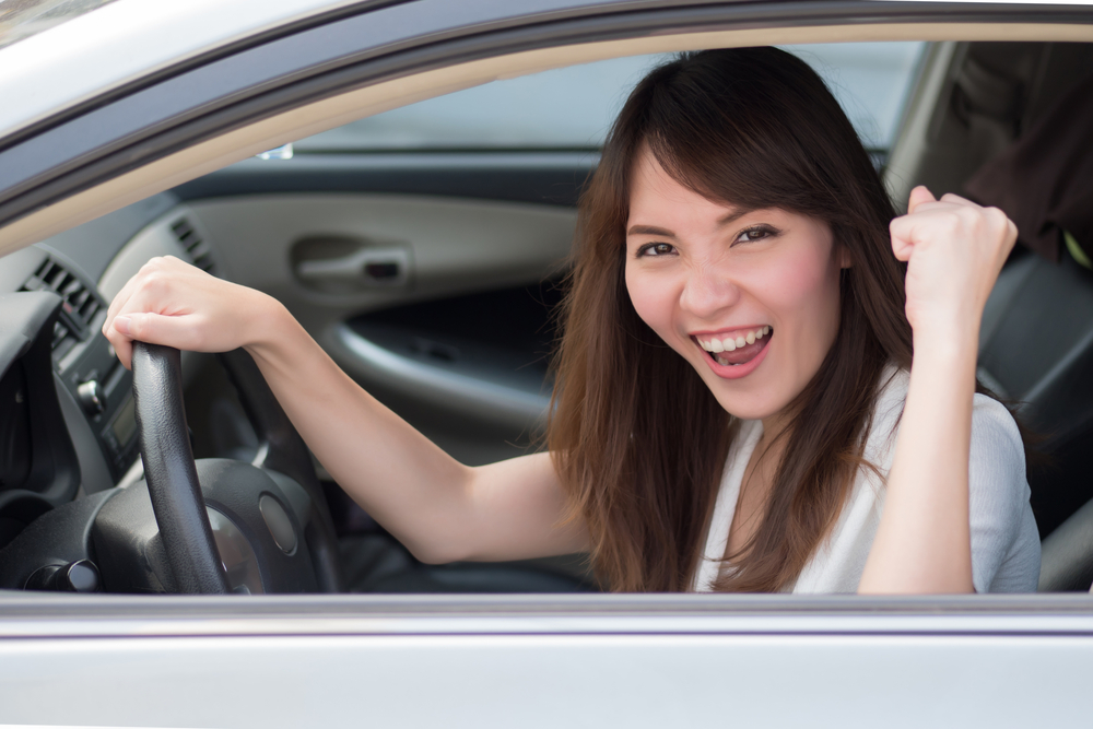 excited woman driver driving personal car; portrait of happy, smiling, excited asian woman driver driving her car, right hand driving or right hand traffic style; 30s adult asian Chinese woman model